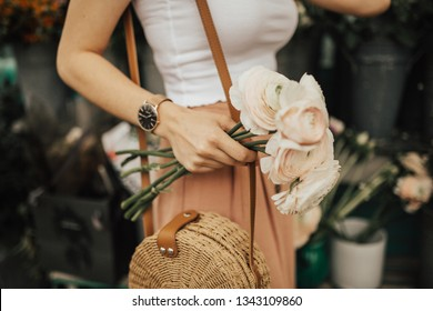 Fashionable young blogger girl holding a bunch of flowers at the flower market. Concept of blogging and street style fashion. Summer and spring outfit ideas.