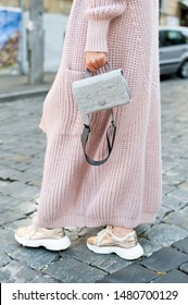 Fashionable young blond woman wearing rose cardigan, beige midi skirt, grey leather belt bag and golden color sneakers. Street style.