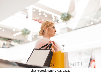 Fashionable young blonde woman in chic stylish pink fur coat with multi-colored paper bags in modern shop center. Luxurious attractive stylish girl fashion model rides on escalator on store.