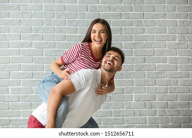 Fashionable young couple against brick wall