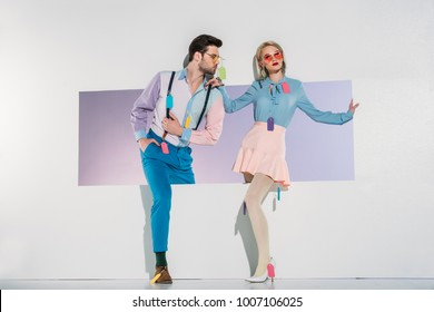 fashionable young couple with colorful tags on clothes walking through opening on grey
