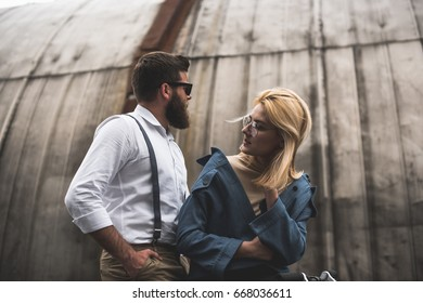 fashionable young couple posing in eyeglasses and sunglasses and looking away