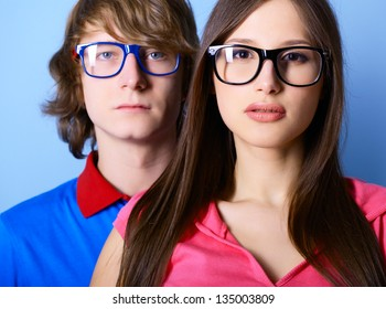 Fashionable young couple wearing trendy sunglasses, over blue