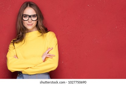 Fashionable young crazy woman posing on red background wearing yellow blouse and eyeglasses. Happy girl posing to the camera.