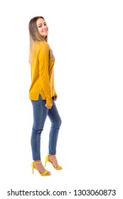 Fashionable young girl in a yellow sweater posing over white background.