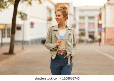 Fashionable young happy woman with a smile in a stylish jacket and jeans walking on the street