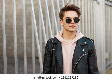 Fashionable young hipster man with a stylish hairstyle in black glasses in a trendy black leather jacket in a pink sweatshirt stands near a metal vintage gate. Attractive american guy. Fashion