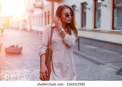 Fashionable young hipster woman in stylish sunglasses in trendy white dress with a fashionable brown leather bag in a city stand on the background of the sun's rays. Attractive stylish girl.
