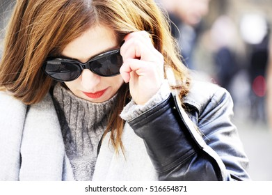 Fashionable young hipster woman in trendy outfit is looking down while fits her sunglasses. City life background.