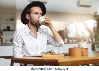 Fashionable young man with beard wearing hat and white shirt having hot drink, sitting at table and holding gadget in his hand. Caucasian male using mobile phone, drinking tea or coffee at cozy cafe