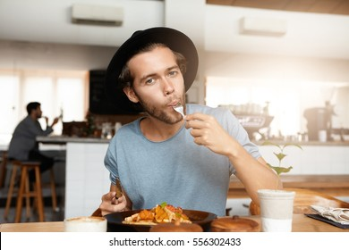 Fashionable young man enjoying tasty food for lunch sitting at wooden table of cozy restaurant. Hungry hipster wearing trendy black hat stilling his hunger while having meal at cafeteria alone
