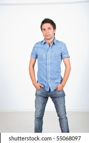 Fashionable young man in jeans and squares shirt posing