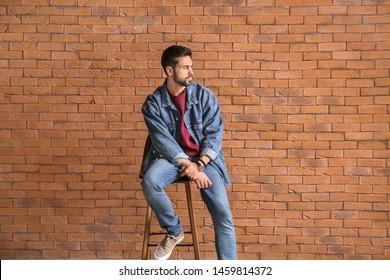 Fashionable young man near brick wall