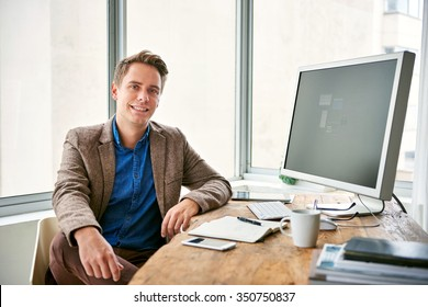 Fashionable young man sitting at his desk in a light and bright office space with windows, looking positive and confident