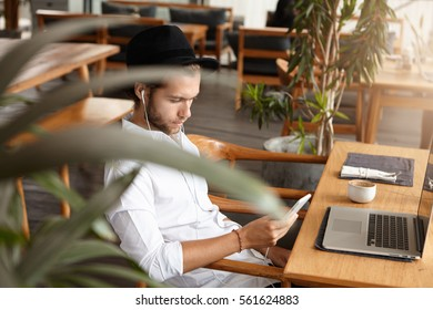 Fashionable young man texting SMS on smart phone while listening to music online on white earphones, enjoying free wireless internet connection at coffee shop, sitting in front of generic laptop
