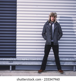 Fashionable young man wearing fur hat and warm overcoat, corrugated iron wall on background - cross processed image