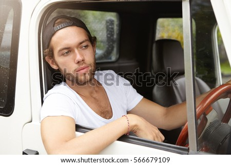 8930994c476 Fashionable young man wearing snapback backwards driving his sport utility  vehicle and sticking his head and