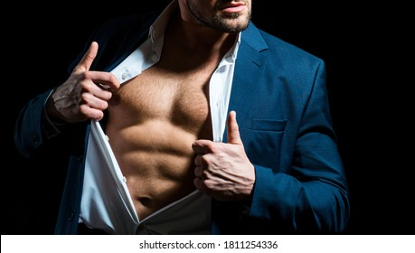 Fashionable young man wearing suit posing over black background. Handsome man posing in white shirt and dark blue suit. Sexy naked torso, six pack abs with open shirt
