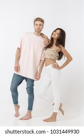 Fashionable young mixed-race couple indoors standing in studio against white background. Portrait of interracial couple, Caucasian man holding with pashion his asian girlfriend from behind, posing at