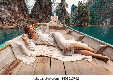 fashionable young model in boho style dress lying on boat at the lake