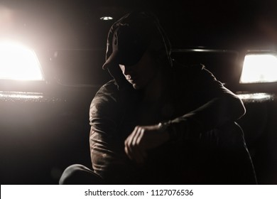 Fashionable young model man in a black cap in stylish clothes with a hooded sits near a car with lights at night