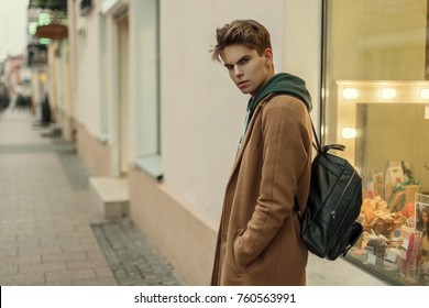 Fashionable young model of a man in a fashion coat with a stylish leather bag posing on the street