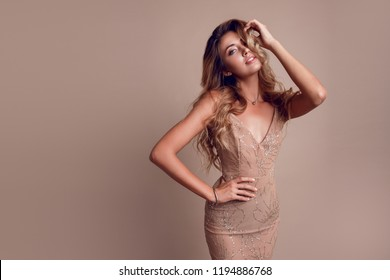 Fashionable  young model with perfect blond hairs in elegant sequin beige dress posing in studio.