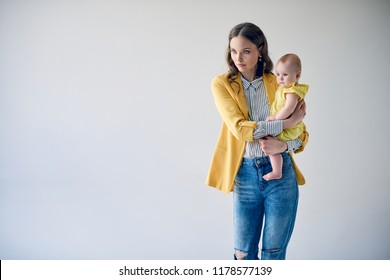 fashionable young mother carrying adorable infant daughter and looking away isolated on grey
