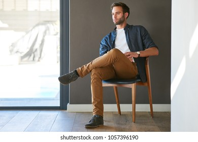 Fashionable young professional looking off into the distance while seated in a beautiful wooden chair in his modern home with a lovely grey textured wall behind him and a large glass pane window.