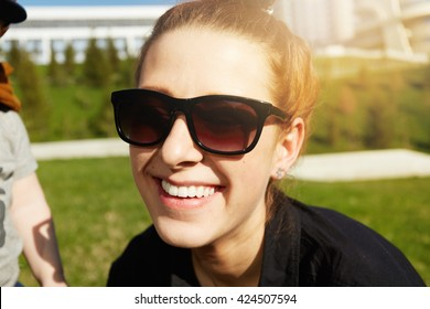 Fashionable young redhead woman in black sunglasses and shirt posing outdoors against green park background on spring sunny day. Stylish mother having fun with her little son in the public garden