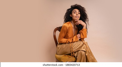 Fashionable young seductive african model with perfect curly hairs in elegant orange blouse and silk pants sitting on vintage chair onver beige background.
