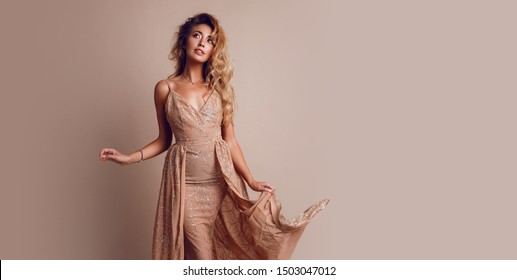 Fashionable young  seductive model with perfect blond hairs in elegant sequin beige dress posing in studio. Trendy make up, full lips, healthy hairs.