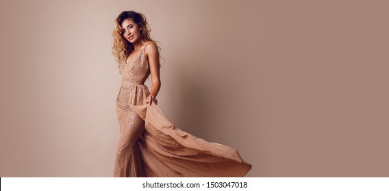 Fashionable young  seductive model with perfect blond hairs in elegant sequin beige dress posing in studio.Trendy make up, full lips, healthy hairs.