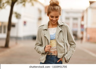 Fashionable young stylish woman with a jacket walks in the city and enjoys the mood