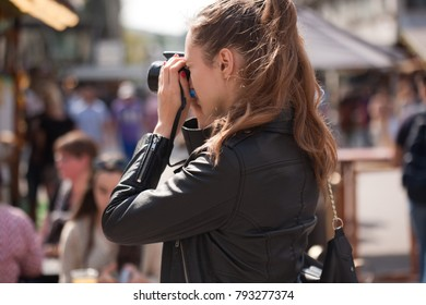 Fashionable young tourist woman photographing the city.
