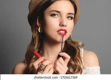 Fashionable young woman applying lipstick against grey background