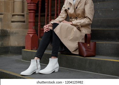 Fashionable young woman in black jeans, beige trench coat and white cowboy boots  with brown handbag sitting on the steps .Outdoor . Fashion. Stylish .
