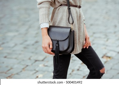 Fashionable young woman in black jeans, beige cardigan and black handbag . Street style .
