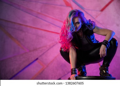 Fashionable young woman in black leather clothes and with colored hair. Bright girl in the image of a comic superhero, neon background