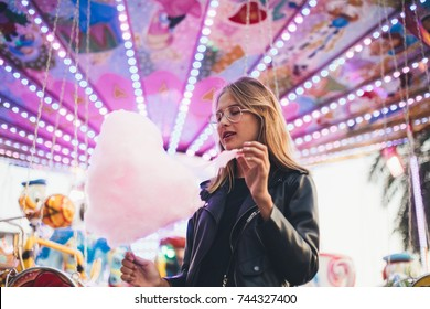 Fashionable young woman in black trendy leather jacket stands in middle of county fair, next to attraction rides or carousel, holds big pink cotton candy or sugar floss, enjoys date night or holidays