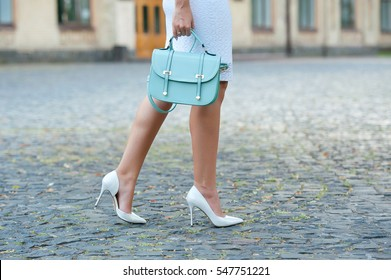 Fashionable young woman in  blouse and white skirt and  high heel shoes with colorful handbag in hand on the city streets. Fashion.