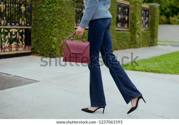 Fashionable young woman in blue flared jeans, grey sweater, white blouse and burgundy handbag .She is wearing black high heel shoes. Street style .