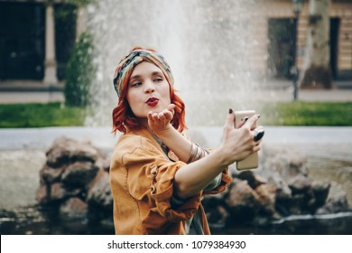 fashionable young woman chatting over smartphone to her long distance boyfriend. beautiful hippie girl sending her love and blowing a kiss while on video call. warm summer festival atmosphere.