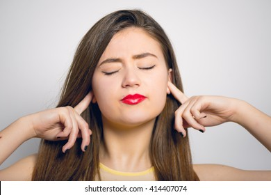 Fashionable young woman closes hands over her ears, in yellow close-up isolated