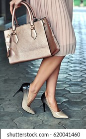 Fashionable young woman in elegant skirt and high heel shoes with handbag in hand on the city streets. Selective focus