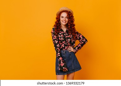 Fashionable young woman with gold earrings, dressed in denim skirt, blouse and boater smiles on isolated background