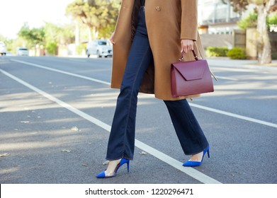 Fashionable young woman in high heel blue shoes, beige coat, blue jeans and burgundy handbag in hand on the city street. Street style.