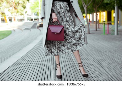 Fashionable young woman in high heel black shoes, black blouse, midi skirt with snake print and burgundy handbag in hand on the city street. Street style.