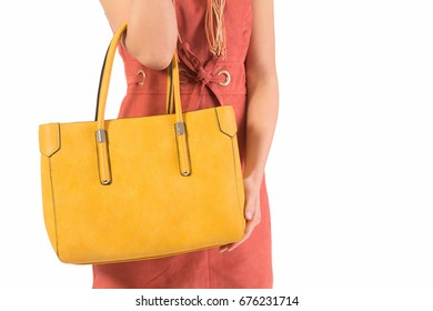 The fashionable young woman holding yellow handbag isolated on white