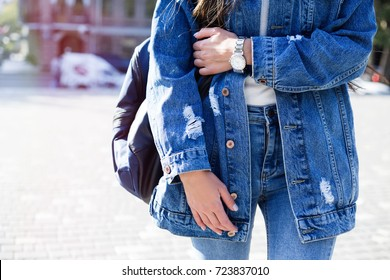 Fashionable young woman in jeans, long jeans jacket and handbag on the city streets. Fashion.Stylish .